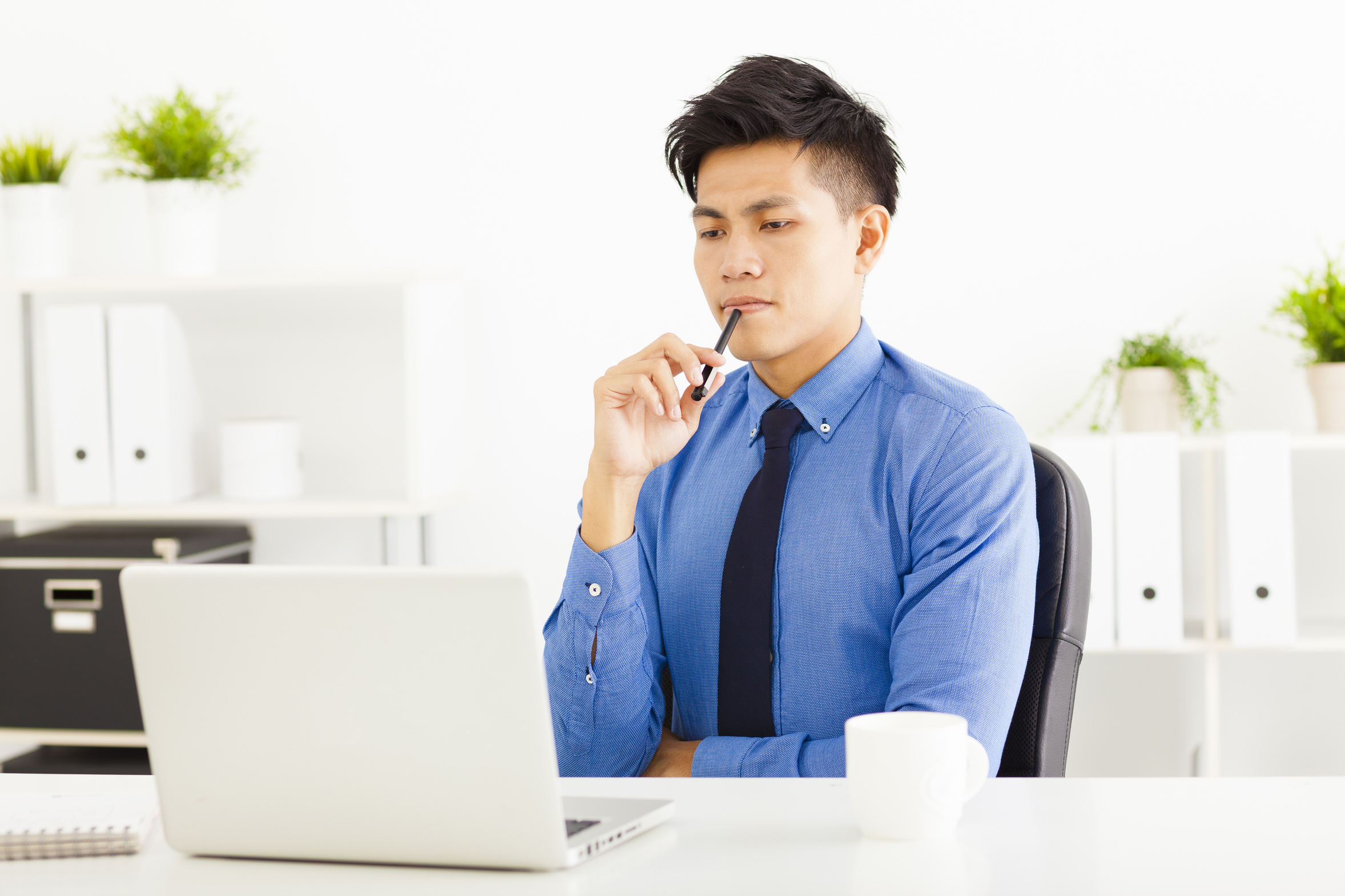 Young business man watching laptop and planning